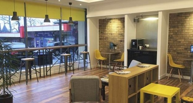 Dental waiting area with a relaxed cafe vibe and yellow accents